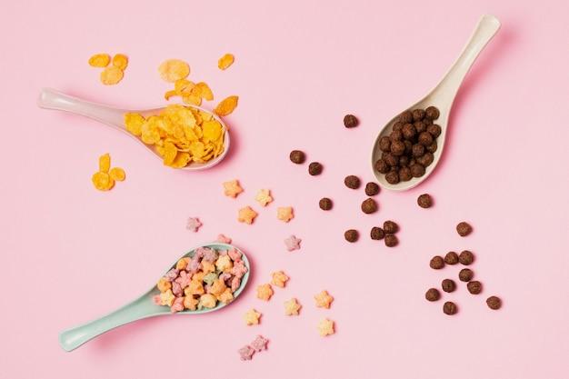 Vista superior arreglo con cereales en cucharas