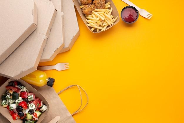 Vista superior arreglo de comida con cajas de pizza