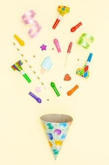Vista superior arreglo de cumpleaños con gorro de fiesta y globos