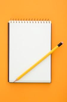 Vista superior del arreglo de escritorio con bloc de notas vacío sobre fondo naranja