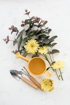 Vista superior del arreglo de herramientas de jardinería y flores florecientes