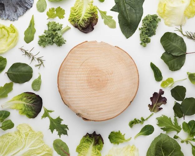 Vista superior del arreglo de hojas de ensalada y tabla de cortar