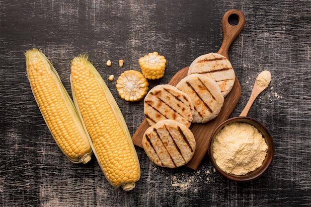 Vista superior de arreglo de maíz y arepas.