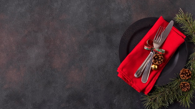 Vista superior del arreglo de mesa navideña con piñas y cubiertos