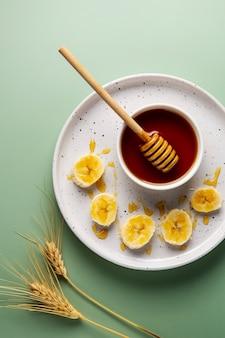 Vista superior arreglo de miel y plátano.