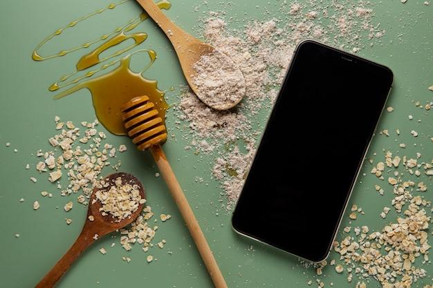 Vista superior del arreglo de miel y teléfono inteligente