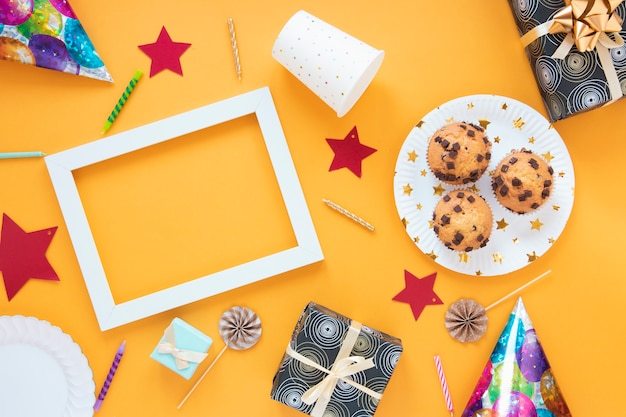 Vista superior arreglo minimalista con regalos de cumpleaños y pastelitos