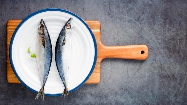 Vista superior arreglo con pescado en tabla de cortar