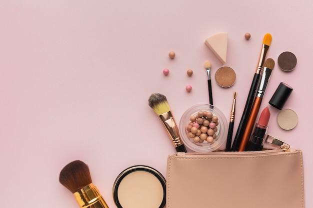 Vista superior arreglo con productos de maquillaje con bolsa de belleza