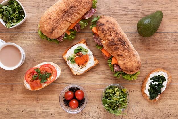 Vista superior arreglo de sándwiches frescos sobre fondo de madera