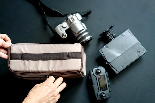 Vista superior de arriba de la mano poner accesorios de la cámara en la bolsa sobre fondo oscuro