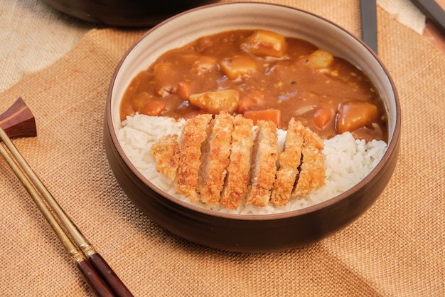 Vista superior de arroz al curry japonés con carne de cerdo frita y verduras en un plato blanco y negro con palillos