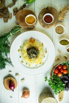 Vista superior de arroz con carne guisada y hierbas