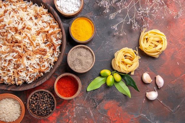 Vista superior de arroz cocido con condimentos en la superficie oscura de la comida del plato de la foto de la comida
