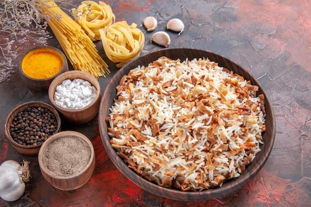 Vista superior del arroz cocido junto con los condimentos en la comida del plato de comida de superficie oscura