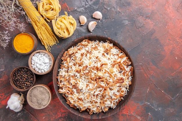 Vista superior del arroz cocido junto con los condimentos en el piso oscuro.