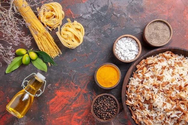Vista superior del arroz cocido junto con los condimentos en un plato de comida de superficie oscura.