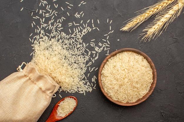 Vista superior del arroz crudo dentro de la bolsa y el plato sobre una superficie gris