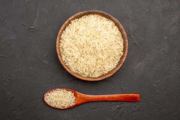 Vista superior del arroz crudo dentro de la placa marrón sobre la superficie gris