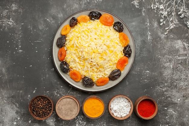 Vista superior de arroz con especias coloridas plato de arroz con frutos secos junto a las ramas de los árboles