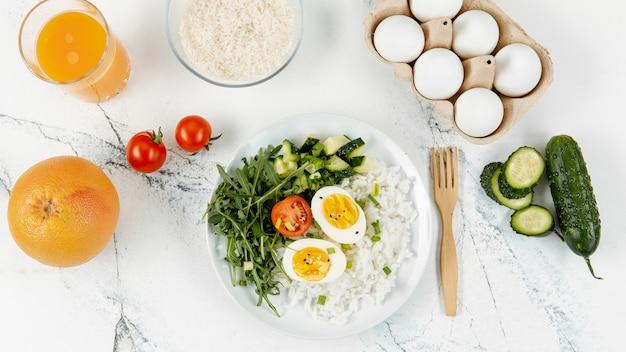 Vista superior de arroz y huevos en un plato con jugo de naranja