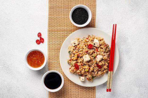 Vista superior de arroz con verduras salsa de soja y palillos