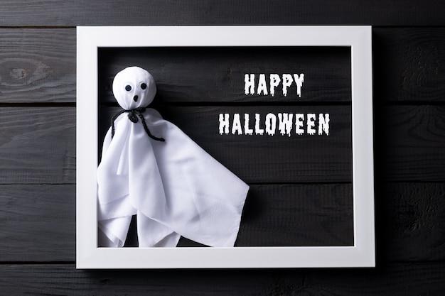 Vista superior de la artesanía de halloween, fantasma de tela en madera negra con texto.