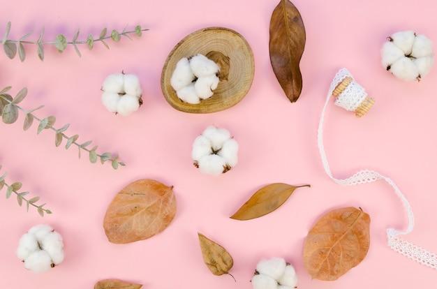 Vista superior de artículos de algodón sobre fondo rosa
