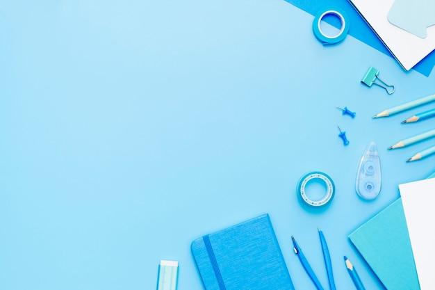 Vista superior de artículos escolares sobre fondo azul.