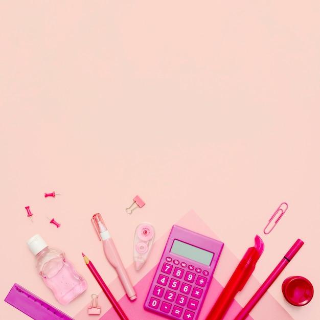 Vista superior de artículos escolares sobre fondo rosa