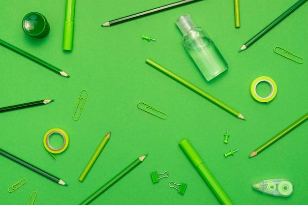 Vista superior de artículos escolares sobre fondo verde