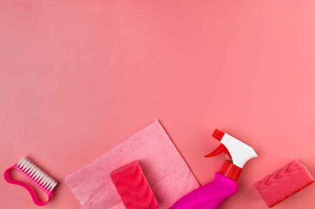 Vista superior de artículos de limpieza sobre fondo rosa
