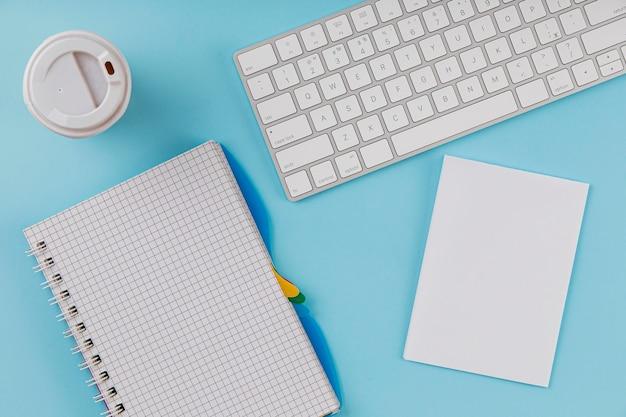 Vista superior de artículos de oficina con teclado y taza de café
