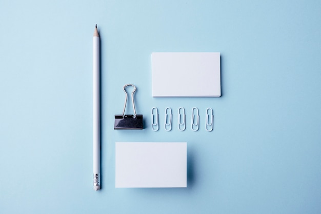 Vista superior de artículos de papelería blancos y tarjetas de visita