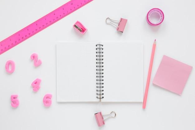 Vista superior de artículos de papelería rosa para matemáticas y ciencias