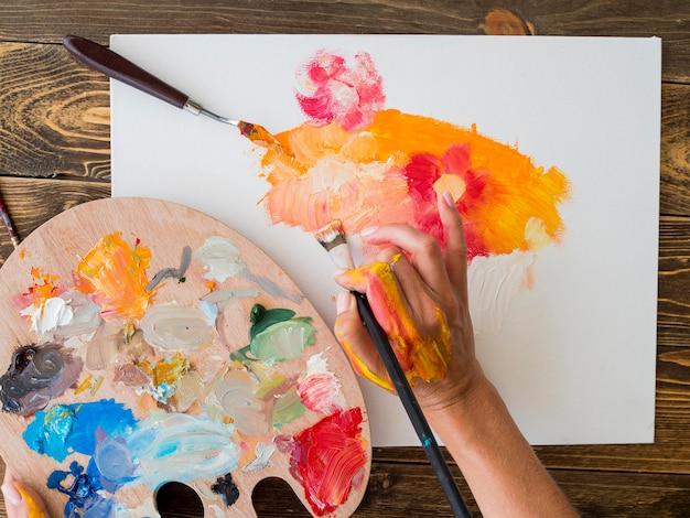 Vista superior del artista pintando con pincel y paleta