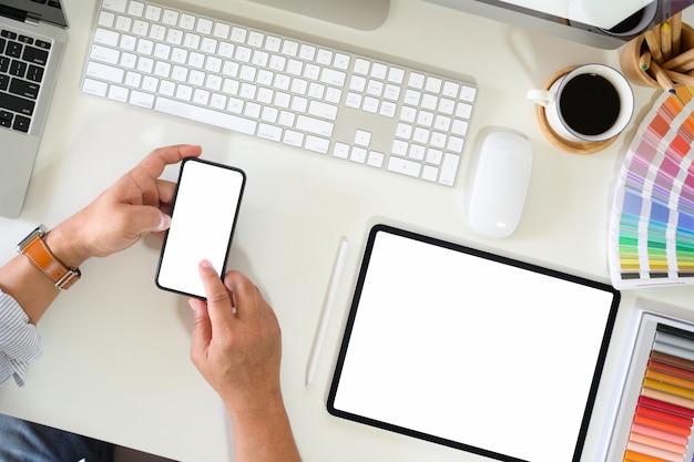 Vista superior de un artista sosteniendo un teléfono móvil en la oficina.