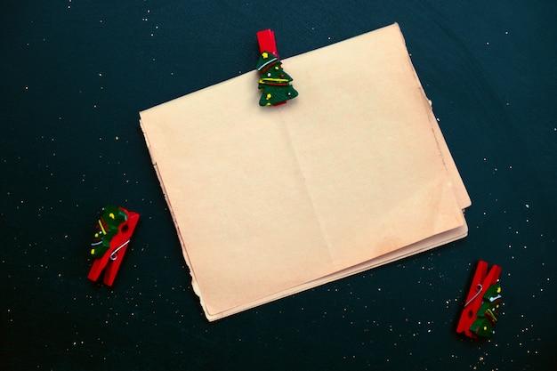 Vista superior áspera hoja en blanco de papel vintage con pin de tela festiva sobre un fondo negro