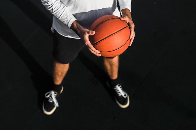 Vista superior atleta sosteniendo baloncesto