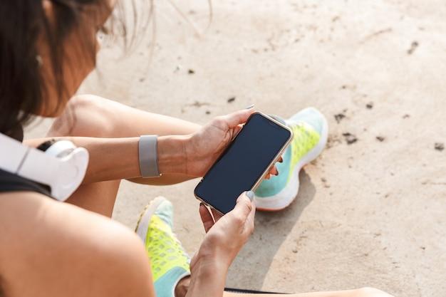 Vista superior de una atractiva mujer joven fitness con teléfono móvil mientras descansa en la playa después de trotar