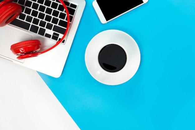 Vista superior de auriculares rojos con teclado portátil en mesa azul y blanco