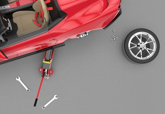 Vista superior de un automóvil levantado con gato hidráulico rojo en el piso
