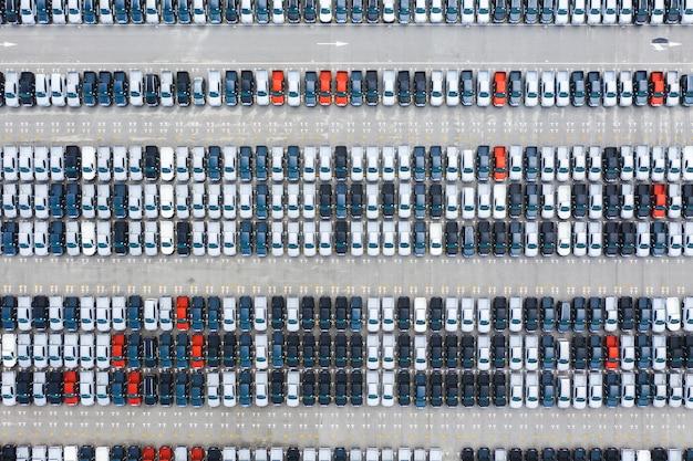 Vista superior de autos nuevos en fila en la terminal de exportación del puerto logístico
