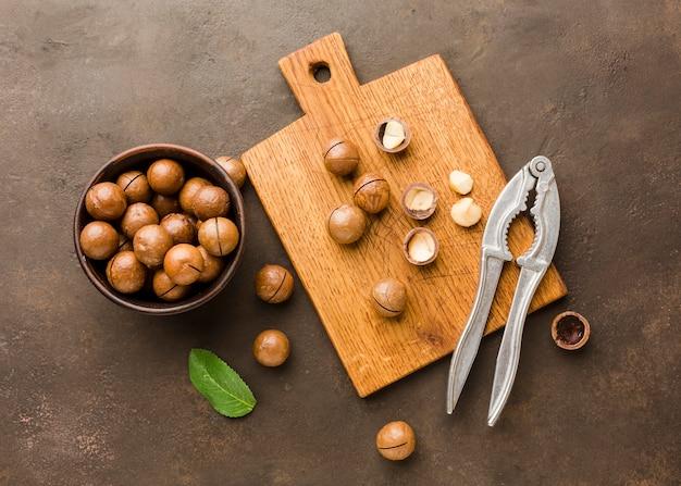 Vista superior avellanas tostadas con tabla de cortar