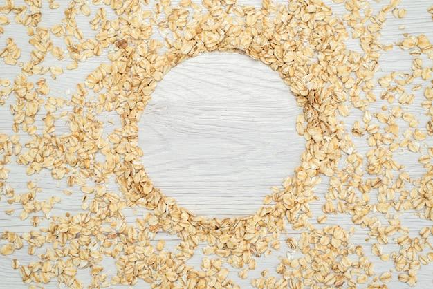 Vista superior de avena cruda en blanco, cereales cereales para el desayuno