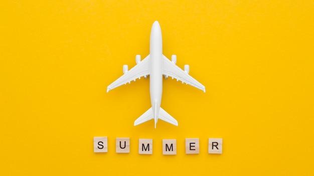 Vista superior del avión de juguete en la mesa con mensaje de verano