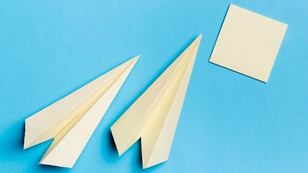 Vista superior de aviones de papel con notas adhesivas en el escritorio