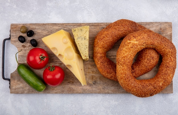 Vista superior de bagels turco de sésamo sobre una tabla de cocina de madera con aceitunas, queso, pepinos y tomates sobre un fondo blanco.