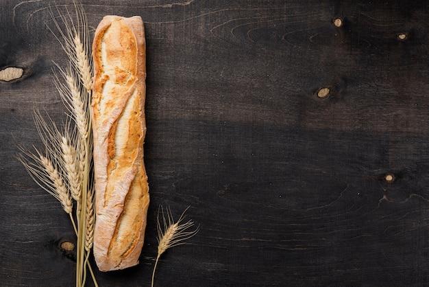 Vista superior baguette pan francés con trigo y copia espacio