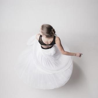 La vista superior de la bailarina adolescente en estudio blanco